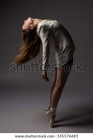 Beautiful slim young female modern jazz contemporary style ballet dancer on pointe shoes wearing a black leotard and white shirt on a neutral grey studio background