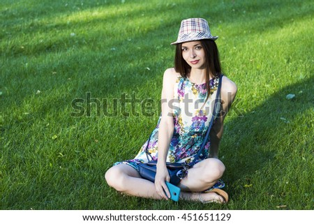 Beautiful slim young girl in  hat and glasses sits with the phone  on a green lawn with the phone waiting for friends. - stock photo