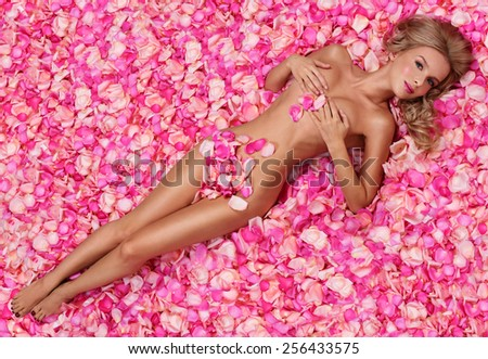 Beautiful slim young woman lying on petals of pink roses. Perfect figure. - stock photo
