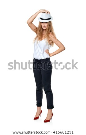 Beautiful slytish woman in full length posing in fedora hat, over white background - stock photo