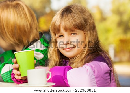 Beautiful small blond girl with green cup - stock photo