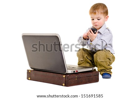 Beautiful small boy dials on a mobile phone while sitting next to laptop - stock photo