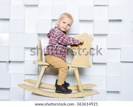 Beautiful small child riding on the toy horse. Happy candid emotions. Studio shot. - stock photo