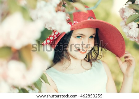 Beautiful small girl in pink fashionable round hat with smiling face in spring flower blossom sunny day