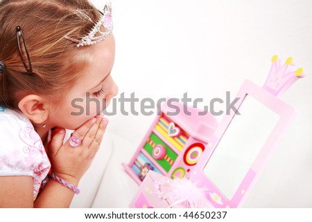 Beautiful small girl looking at the mirror - stock photo