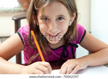 Beautiful small girl smiling at the camera and working on her school project at home - stock photo