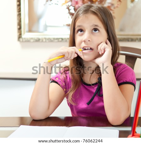 Beautiful small girl thinking while working on her school project at home - stock photo