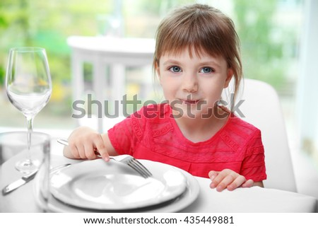 Beautiful small girl waiting for dinner - stock photo