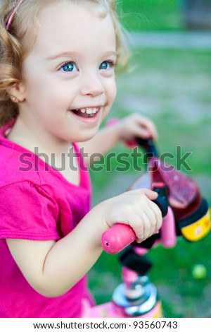 Beautiful small girl wearing colorful clothes laughing and riding her bicycle in the park - stock photo
