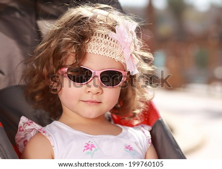 Beautiful small girl with curly hair and pink sunglasses smiling