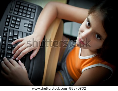 Beautiful small girl working on a personal computer at home - stock photo