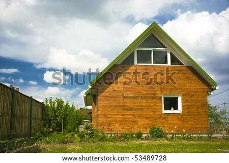 Beautiful small house with flowers under the sky - stock photo