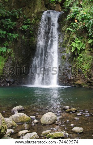 Beautiful small waterfall flows into the forest pond at the end of the hiking path of Faial da Terra, Sao Miguel, Azores. - stock photo