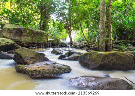 Beautiful small waterfall, landscape in the mountains with lush green bush, rocks and flowing water. - stock photo