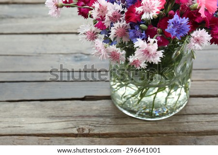 Beautiful small wild flowers in vase on wooden background
