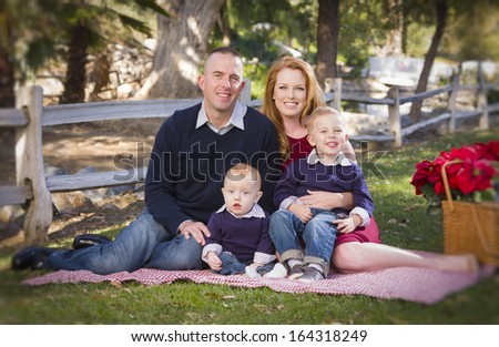 Beautiful Small Young Family Holiday Portrait in the Park.