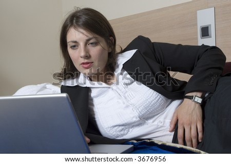 beautiful, smartly dressed young woman lying on a bed typing on a laptop