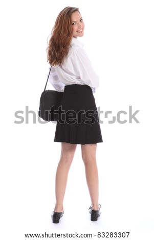 Beautiful smile from young teenage secondary school student girl, looking back over her shoulder wearing black and white school uniform. - stock photo
