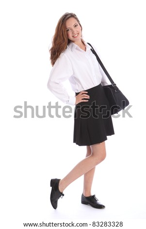 Beautiful smile from young teenage secondary school student girl wearing black and white school uniform, with bag over her shoulder.