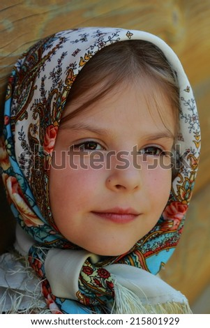beautiful smiley little girl wearing Pavloposadsky scarf over wooden background at summer