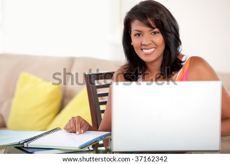 Beautiful smiley woman studying at home with a laptop - stock photo