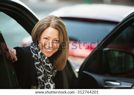 Beautiful smiling adult business woman in car with open door - stock photo