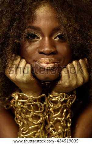 Beautiful smiling african american woman in gold accessories with arms crossed under her chin - stock photo