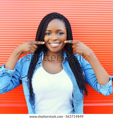 Beautiful smiling african woman showing fingers on teeth over colorful red background - stock photo