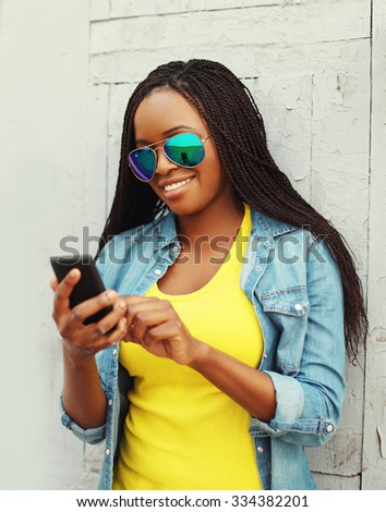 Beautiful smiling african woman using smartphone in city - stock photo