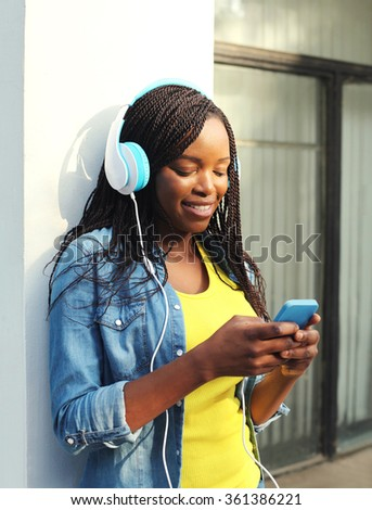 Beautiful smiling african woman with headphones listens to music and using smartphone in city - stock photo