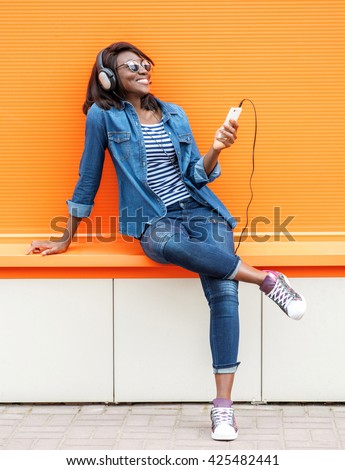 Beautiful smiling african woman with headphones listens to music over orange background.  Fashion woman in sunglasses outdoor. - stock photo