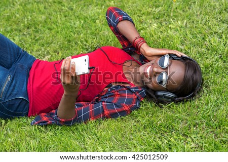 Beautiful smiling african woman with headphones listens to music. Smiling Girl in Green Grass. Fashion woman in sunglasses outdoor. - stock photo