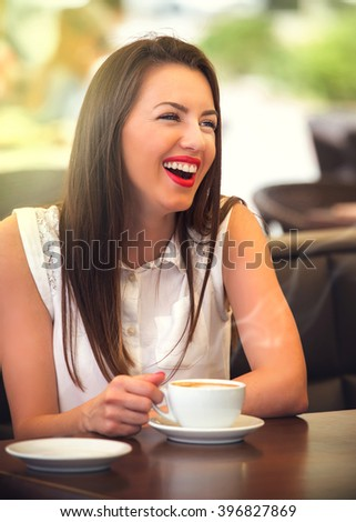 Beautiful smiling and young woman drinking a coffee outdoor in garden of restaurant.