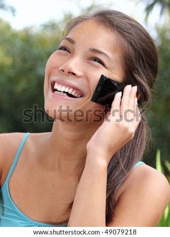 Beautiful smiling asian talking and laughing on the mobile phone.