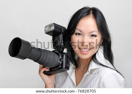 Beautiful smiling asian woman with photo camera - stock photo