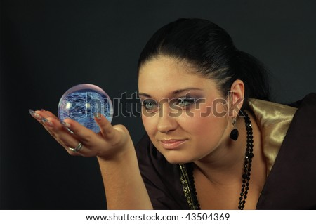 Beautiful smiling black-haired witch holding the magic sphere - stock photo