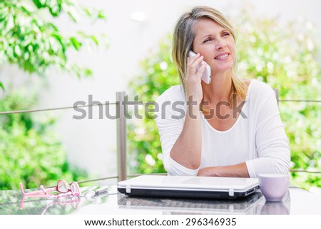 beautiful smiling blond woman talking on the phone - stock photo