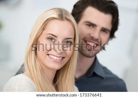 Beautiful smiling blond woman with a lovely wide friendly smile posing with a handsome young man with focus to her face - stock photo