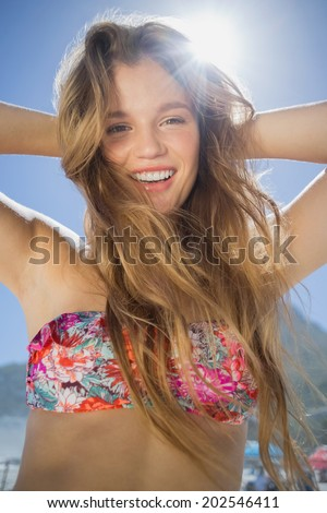Beautiful smiling blonde in floral bikini on the beach on a sunny day - stock photo