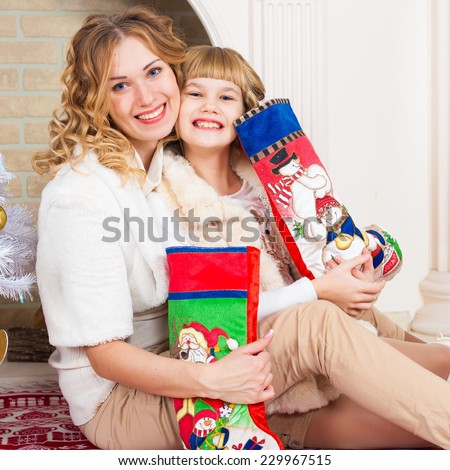 beautiful  smiling  blonde  mother and daughter near  the christmas tree with gifts - stock photo