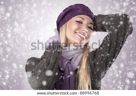 beautiful smiling blonde wearing a grey woolen sweater, a scarf, a knitted cap and gloves - stock photo