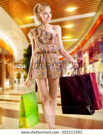 Beautiful smiling blonde woman holding bags, shopping, looking at