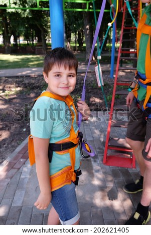 Beautiful smiling boy in safety equipment in adventure park, outdoor shot - stock photo