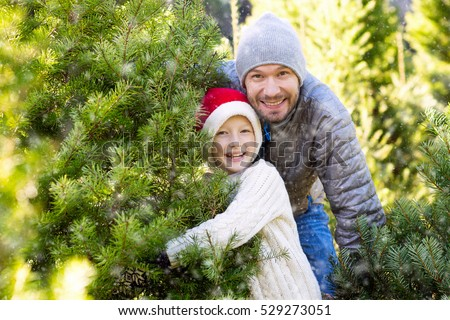 beautiful smiling boy in santa's hat, sweater and mittens and his father choosing christmas tree at market or farm at winter, holiday concept