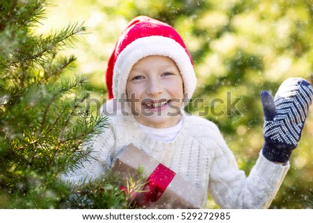 beautiful smiling boy in santa's hat, sweater and mittens holding nicely wrapped christmas gift by the tree or in the forest enjoying snowy cold winter weather, holiday or happiness concept