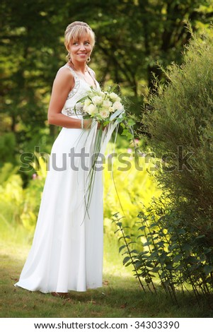 Beautiful smiling bride on green grass meadow with a nice yellow bouquet smiles - stock photo