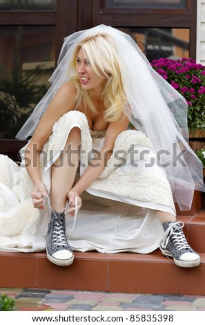 Beautiful smiling bride sitting on the porch and putting on old blue trainers - stock photo