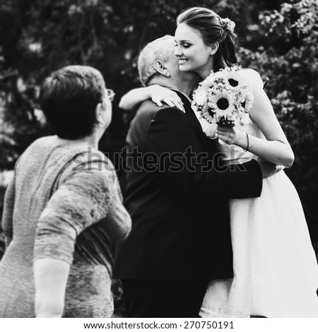 beautiful smiling bride with a bouquet hugging his father black and white - stock photo