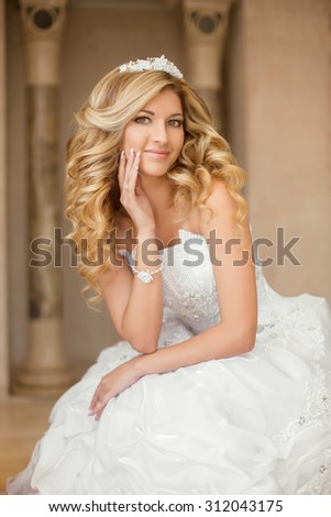 Beautiful smiling bride woman with long curly hair posing in wedding dress at interior. Beauty indoor portrait. - stock photo