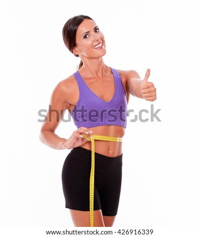 Beautiful smiling brunette gesturing thumbs up, looking at camera, while measuring her waist wearing violet and black gymnastic clothing isolated